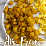 air fryer potatoes with scrambled eggs on a white plate