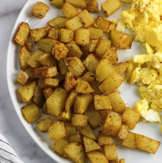airy fryer potatoes on a white plate with scrambled eggs