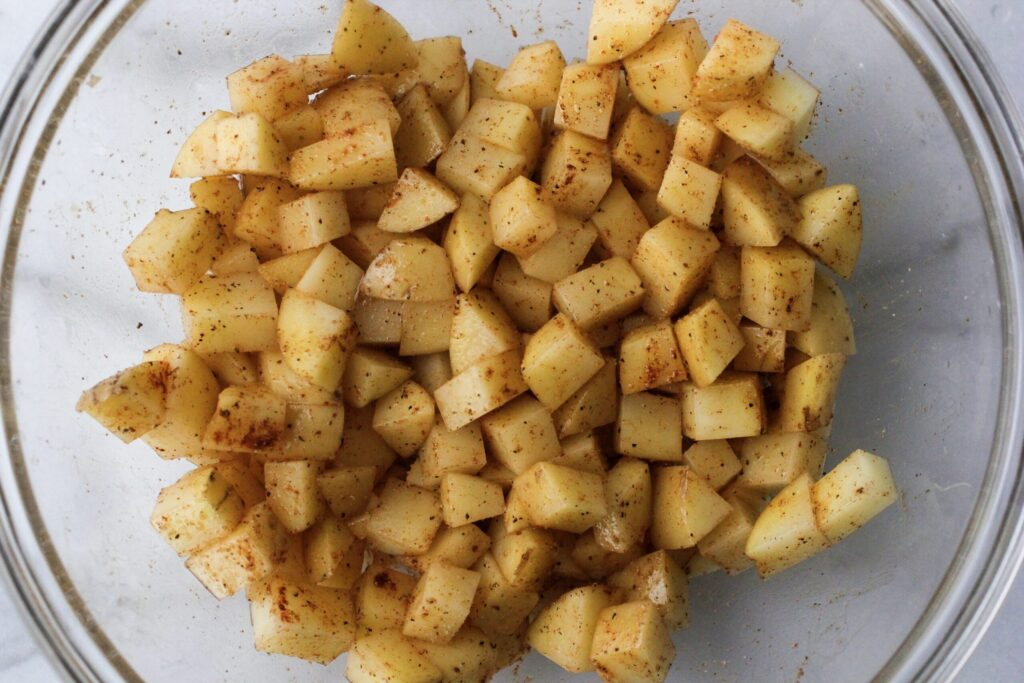 diced potatoes with olive oil and spices in a clear glass bowl