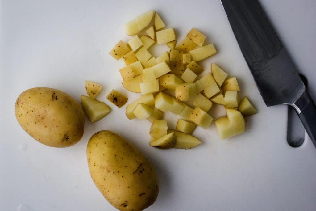 two yukon gold potatoes on a white cutting board with another potato cut into cubes and a big kitchen knive