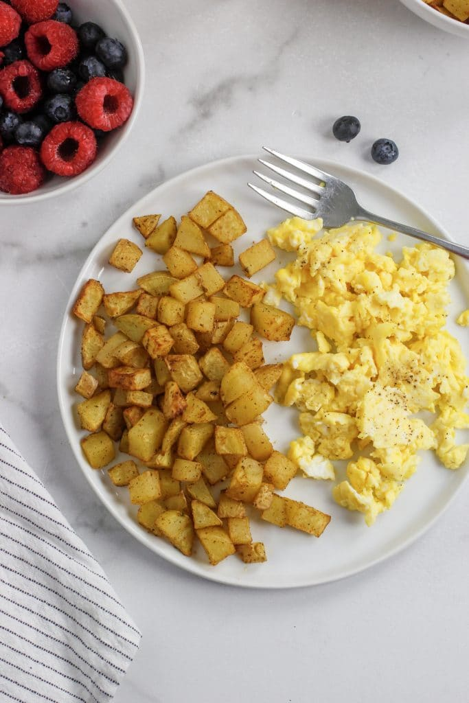 air fryer breakfast potatoes on a white plate with scrambled eggs and a fork with berrys in another bowl