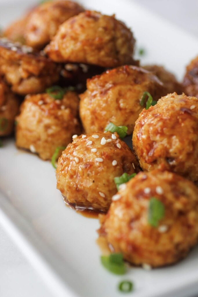 orange chicken meatballs on a white plate served as an appetizer