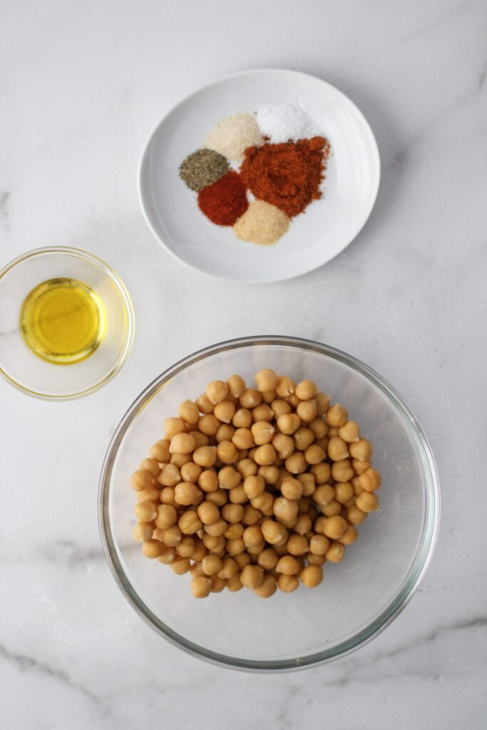 spices on a white plate, olive oil in clear small bowl and chickpeas that have been rinsed and dried in a larger glass bowl