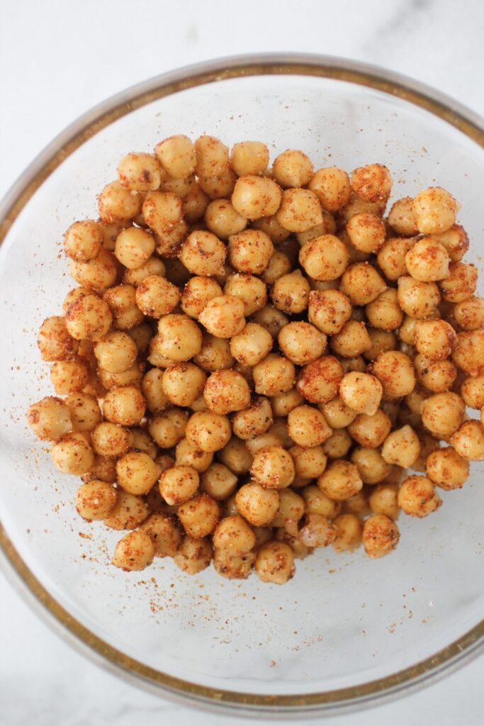 spicy roasted chickpeas with spices and olive oil mixed in a clear glass bowl