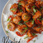 orange chicken meatballs over rice with green onions and toasted sesame seeds as garnish