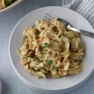 tuna noodle casserole on a white plate with a napkin and fork