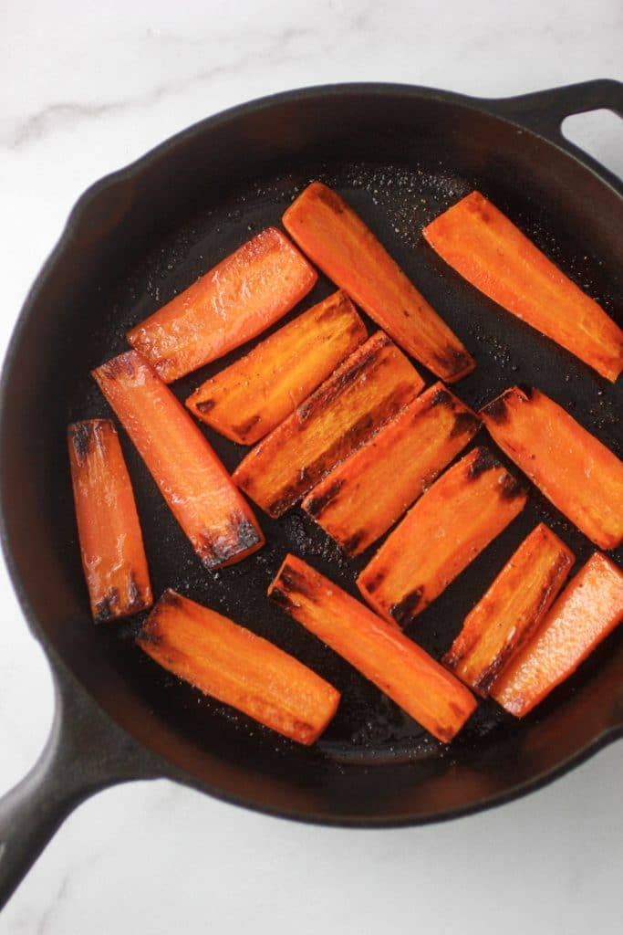 Carrots that have been half way cooked in a cast iron skillet.