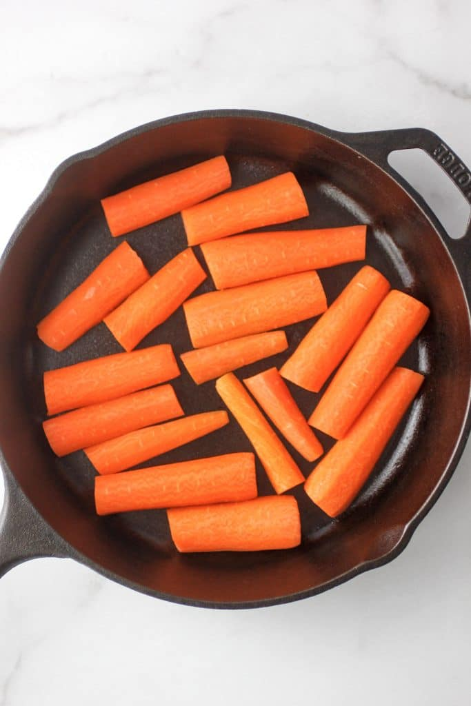 Raw carrots in a cast iron skillet.