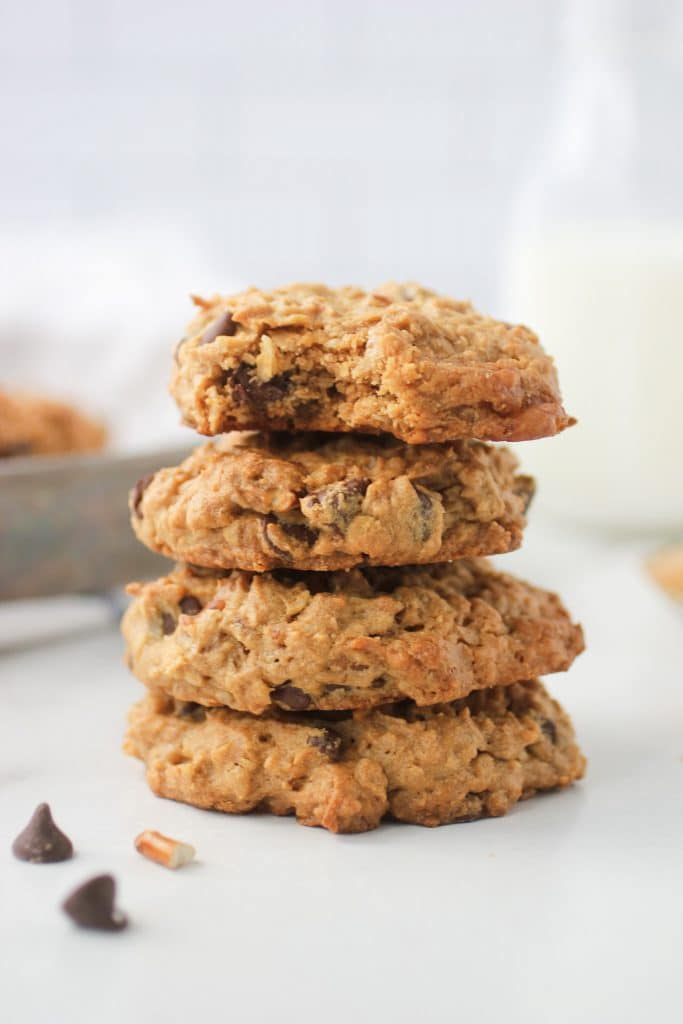 Four Peanut Butter Breakfast Cookies stacked with a bottle of milk in the back ground.