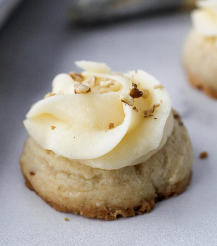 Pecan Thumbprint Cookie with buttercream icing and chopped pecan sprinkled on top.