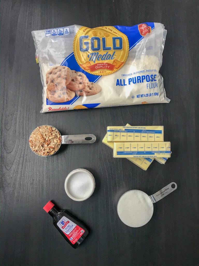 The ingredients needed to make thumbprint pecan cookies.  Sugar, flour, vanilla, salt and butter on a black table.