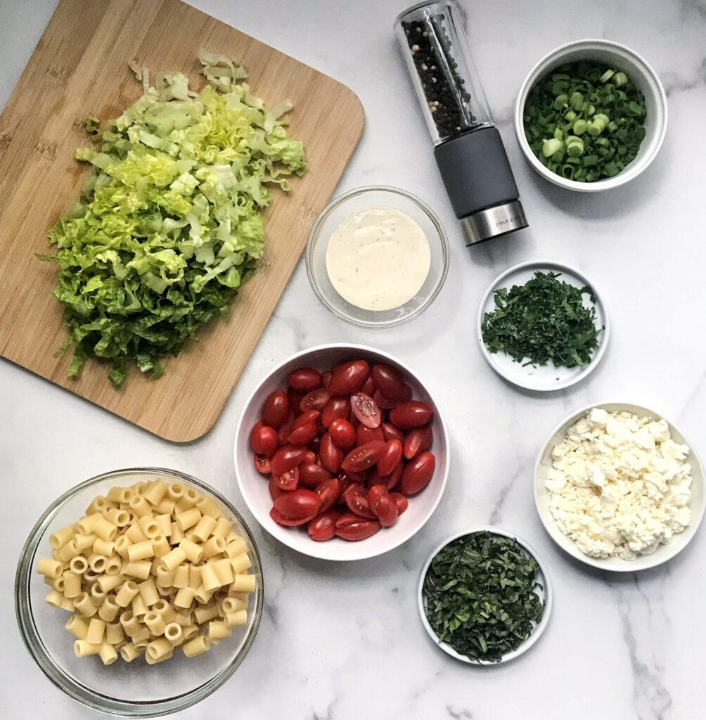 A bowl of each ingredient to make pasta salad including, feta cheese, cherry tomatoes, fresh basil, fresh parsley, ditalini pasta, romaine lettuce chopped, Caesar dressing, sliced green onions and a black pepper shaker.