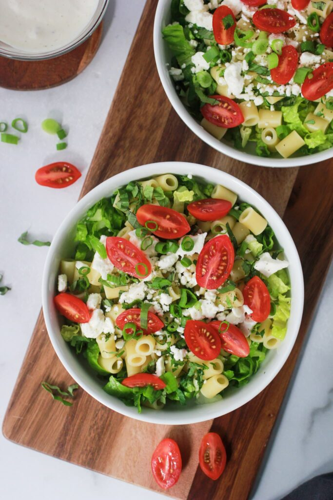 Caesar Pasta Salad in two bowls with tomatoes and green onions around the bowls.  There is also a small bowl of Caesar dressing on the side.  The salads have not been dressed yet.