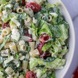 Caesar Pasta Salad with dressing in a white bowl.