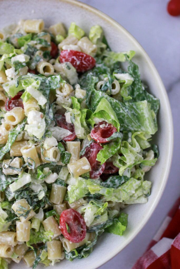 Pasta salad in a white bowl that has been tossed in the Caesar salad dressing.