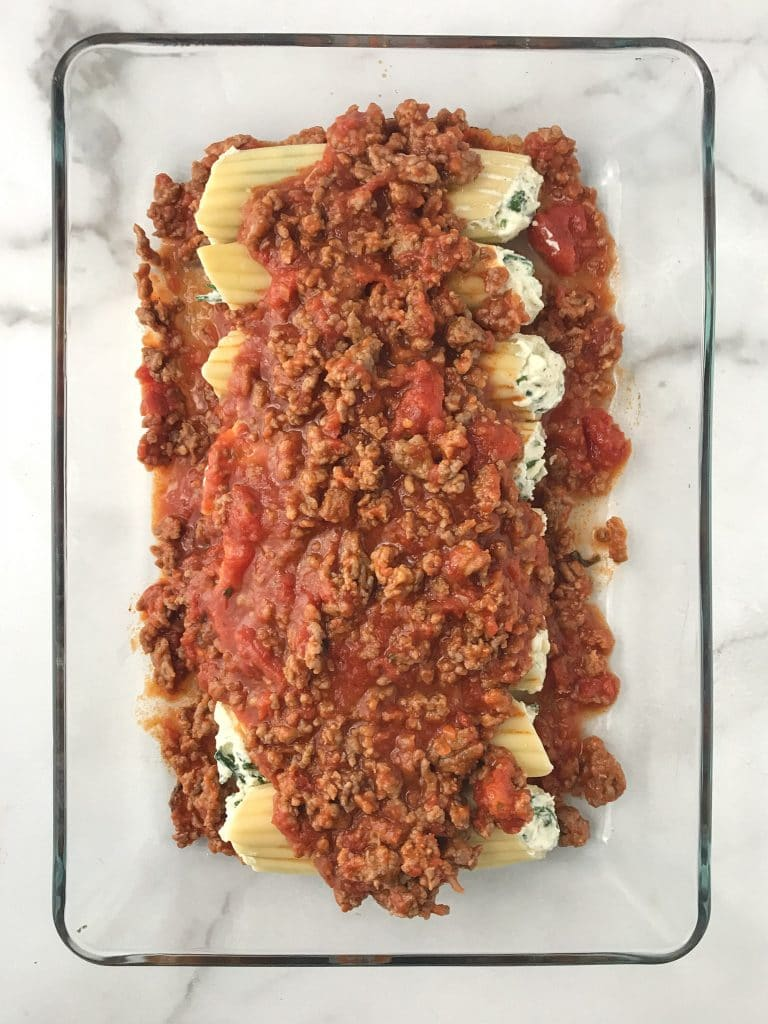 filled manicotti shells with sausage marinara on the top and bottom