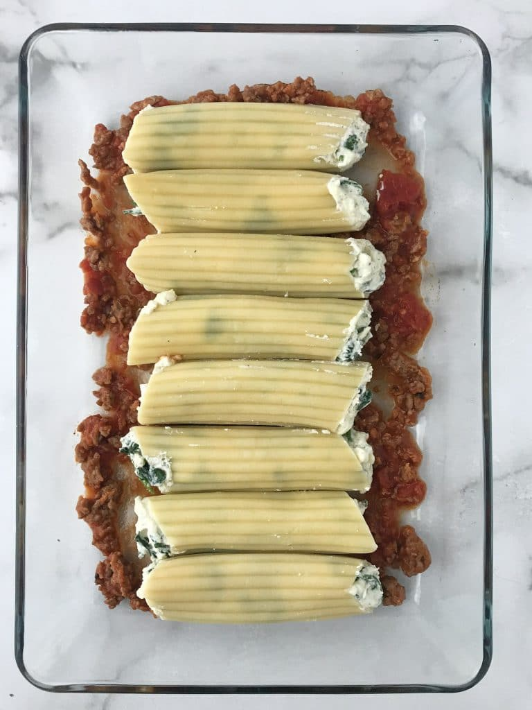 filled manicotti shells over sausage mixture in a clear 9 x 13 pan