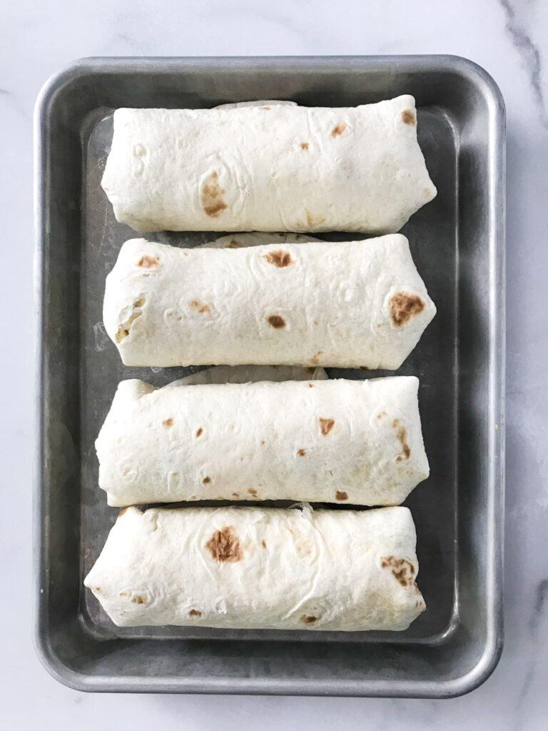 Sausage Breakfast Burritos on a baking sheet.