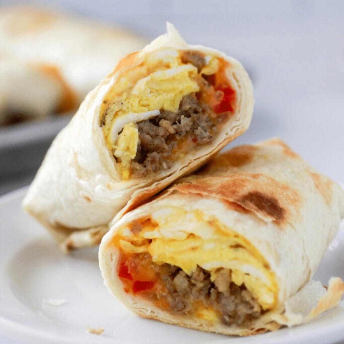 A sausage breakfast burrito cut in half.